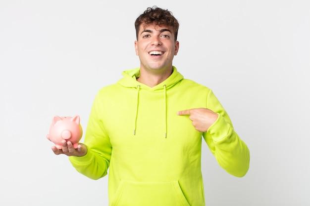 Jonge knappe man die zich gelukkig voelt en naar zichzelf wijst met een opgewonden persoon en een spaarvarken vasthoudt