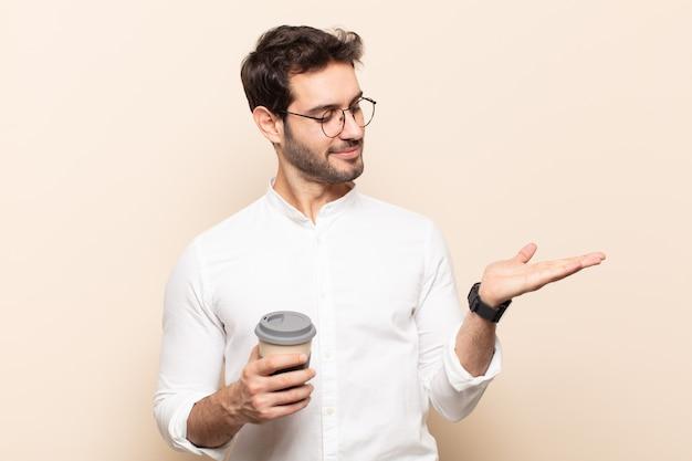 Jonge knappe man die zich gelukkig voelt en nonchalant glimlacht, kijkend naar een object of concept dat aan de zijkant wordt vastgehouden