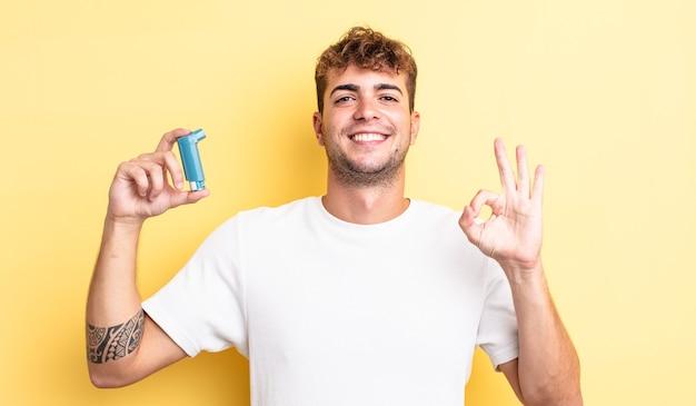 Jonge knappe man die zich gelukkig voelt, goedkeuring toont met een goed gebaar. astma concept