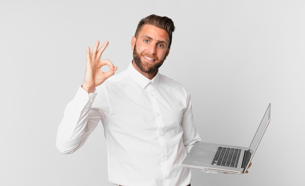 Jonge knappe man die zich gelukkig voelt, goedkeuring toont met een goed gebaar en een laptop vasthoudt