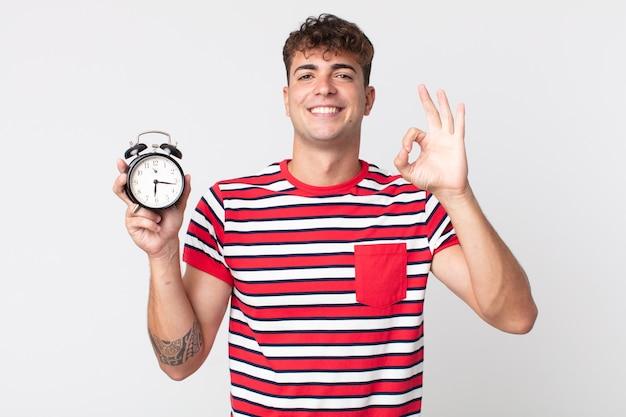 Jonge knappe man die zich gelukkig voelt, goedkeuring toont met een goed gebaar en een wekker vasthoudt