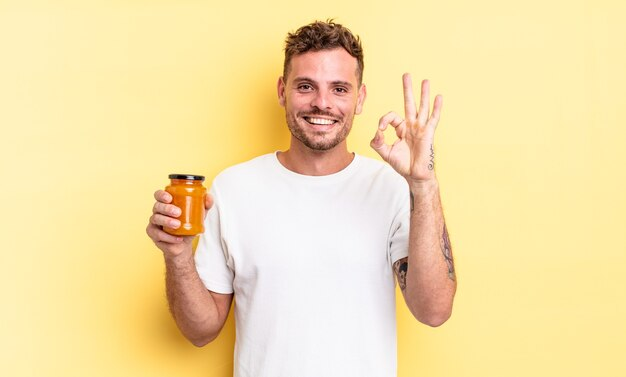 Jonge knappe man die zich gelukkig voelt, goedkeuring toont met een goed gebaar. perzik gelei concept