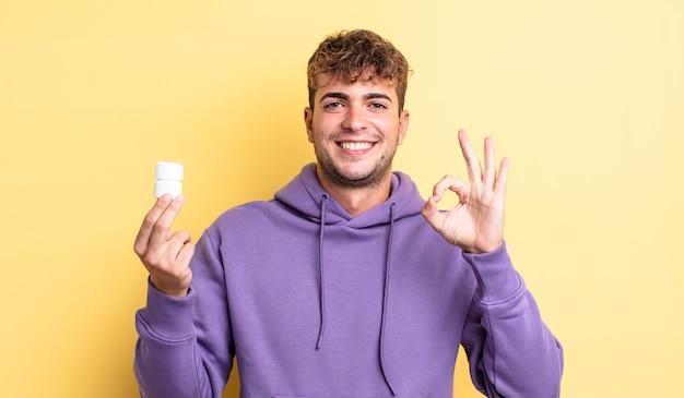 Jonge knappe man die zich gelukkig voelt, goedkeuring toont met een goed gebaar. pillen fles concept