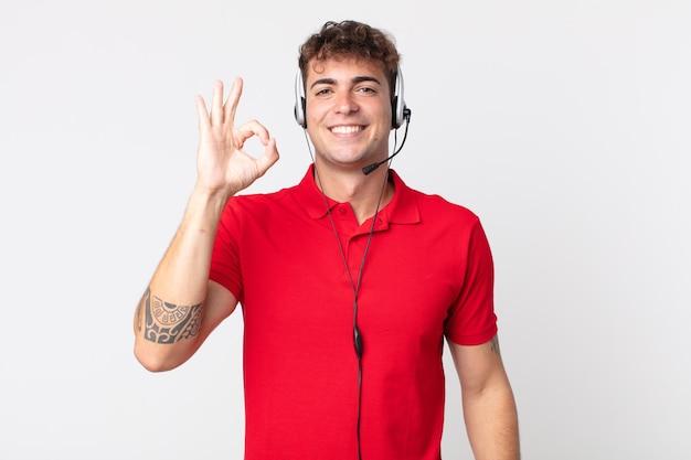 Jonge knappe man die zich gelukkig voelt, goedkeuring toont met een goed gebaar. telemarketeer concept