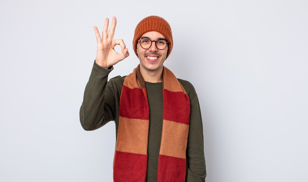 Jonge knappe man die zich gelukkig voelt, goedkeuring toont met een goed gebaar. winterkleren concept