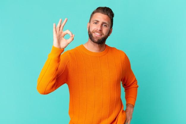 Jonge knappe man die zich gelukkig voelt, goedkeuring toont met een goed gebaar