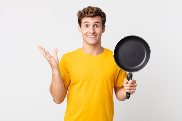 Jonge knappe man die zich gelukkig voelt, verrast een oplossing of idee realiseert en een kookpan vasthoudt