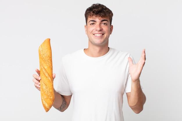 Jonge knappe man die zich gelukkig voelt, verrast een oplossing of idee realiseert en een stokbrood vasthoudt