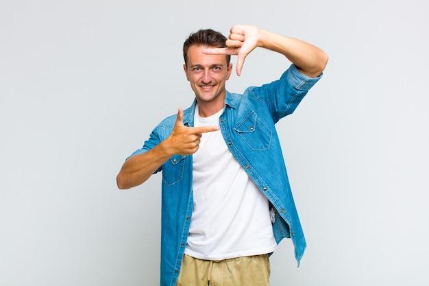 Jonge knappe man die zich gelukkig, vriendelijk en positief voelt, lacht en een portret of fotolijst met handen maakt