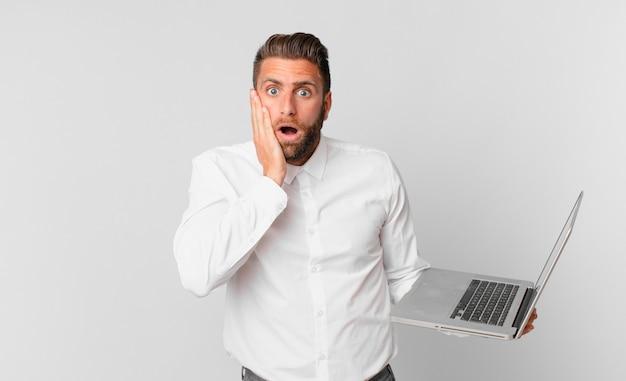 Jonge knappe man die zich geschokt en bang voelt en een laptop vasthoudt