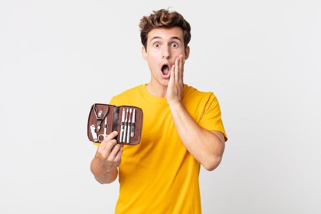 Jonge knappe man die zich geschokt en bang voelt en een nagelkoffer vasthoudt