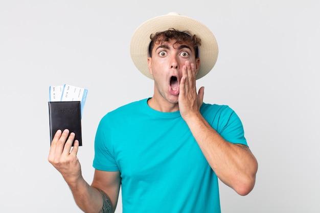 Jonge knappe man die zich geschokt en bang voelt. reiziger met zijn paspoort