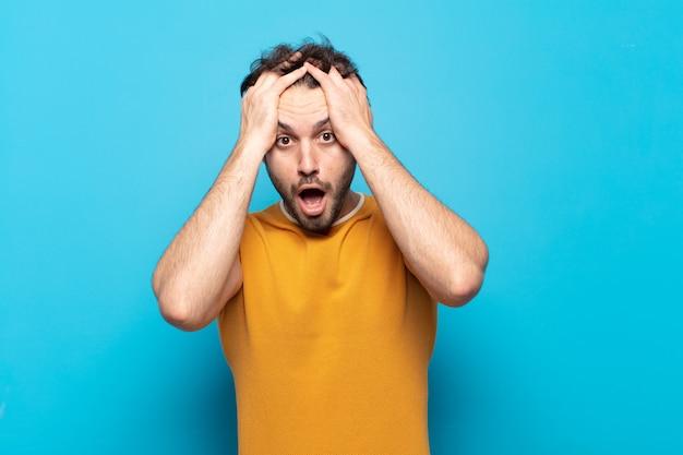 Jonge knappe man die zich geschokt en geschokt voelt, zijn hand opheft en in paniek raakt bij een fout
