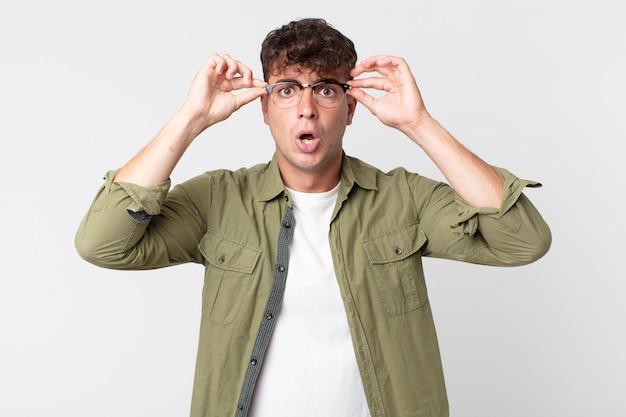 Jonge knappe man die zich geschokt, verbaasd en verrast voelt, een bril vasthoudt met een verbaasde, ongelovige blik