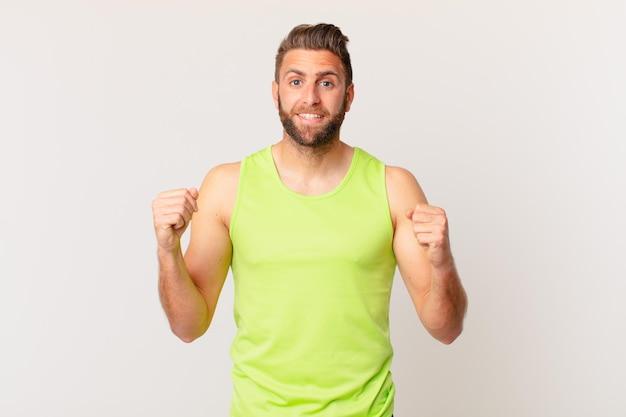Jonge knappe man die zich geschokt voelt, lacht en succes viert. fitnessconcept