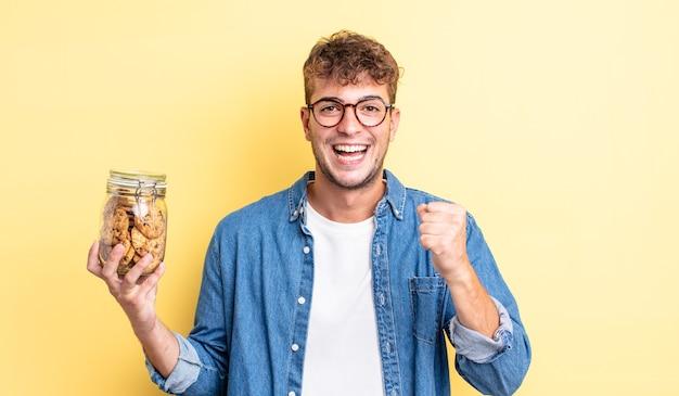 Jonge knappe man die zich geschokt voelt, lacht en succes viert. koekjes fles concept