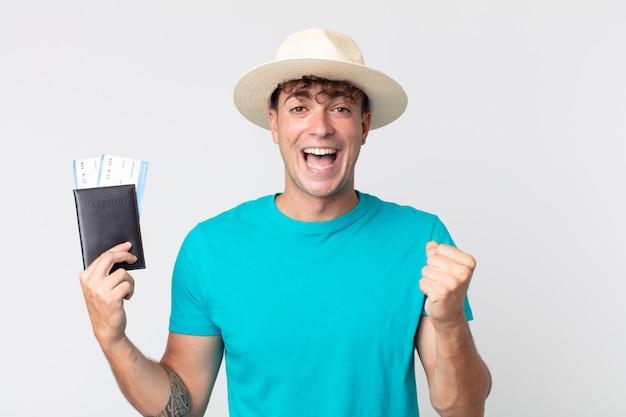 Jonge knappe man die zich geschokt voelt, lacht en succes viert. reiziger met zijn paspoort