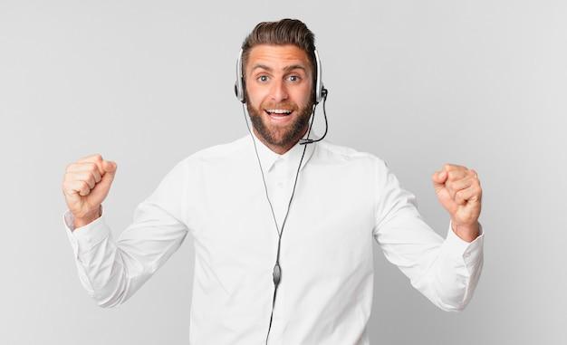 Jonge knappe man die zich geschokt voelt, lacht en succes viert. telemarketing concept