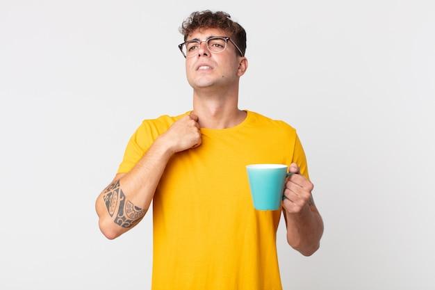 Jonge knappe man die zich gestrest, angstig, moe en gefrustreerd voelt en een kopje koffie vasthoudt