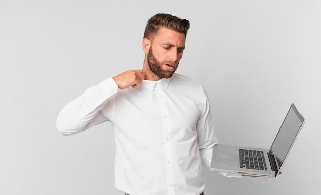 Jonge knappe man die zich gestrest, angstig, moe en gefrustreerd voelt en een laptop vasthoudt
