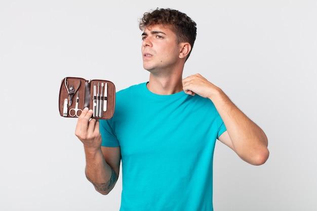 Jonge knappe man die zich gestrest, angstig, moe en gefrustreerd voelt en een nagelkoffer vasthoudt