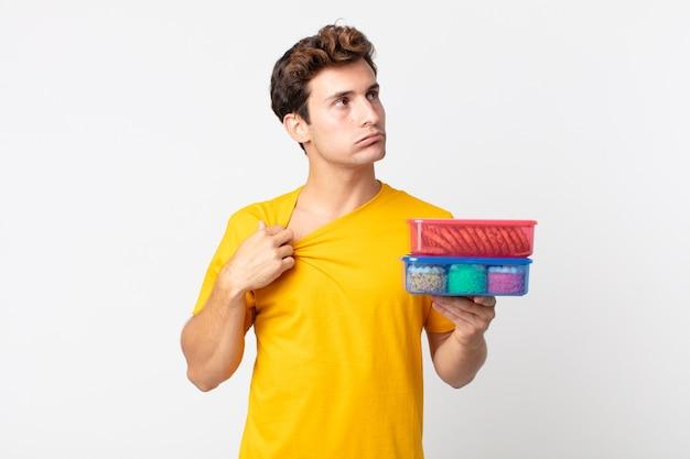 Jonge knappe man die zich gestrest, angstig, moe en gefrustreerd voelt en lunchboxen vasthoudt