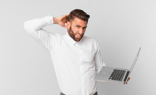 Jonge knappe man die zich gestrest, angstig of bang voelt, met de handen op het hoofd en een laptop vasthoudt