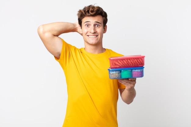 Jonge knappe man die zich gestrest, angstig of bang voelt, met de handen op het hoofd en lunchboxen vasthoudt