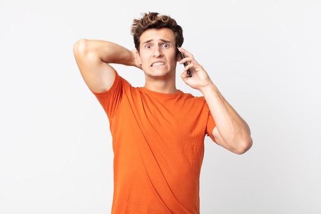 Jonge knappe man die zich gestrest, angstig of bang voelt, met de handen op het hoofd en praat met een smartphone