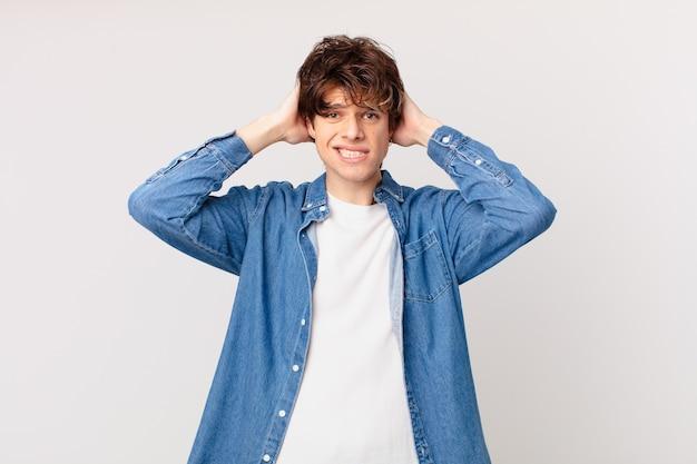 Jonge knappe man die zich gestrest, angstig of bang voelt, met de handen op het hoofd