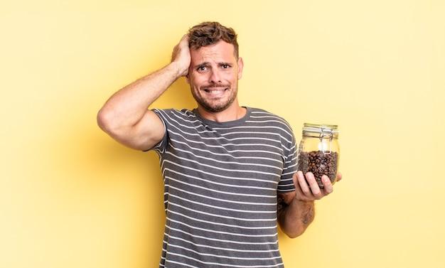 Jonge knappe man die zich gestrest, angstig of bang voelt, met handen op het hoofd koffiebonen concept