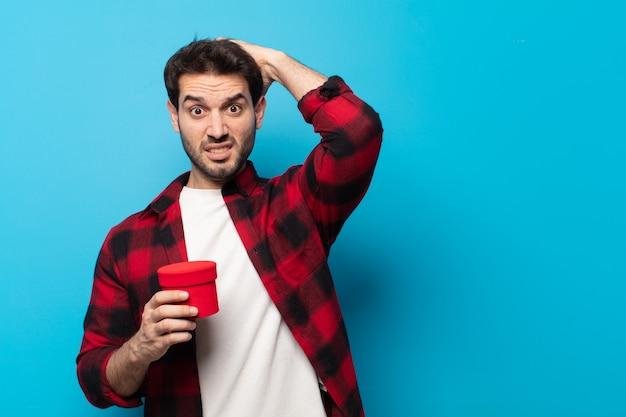 Jonge knappe man die zich gestrest, bezorgd, angstig of bang voelt, met de handen op het hoofd, in paniek raakt bij vergissing