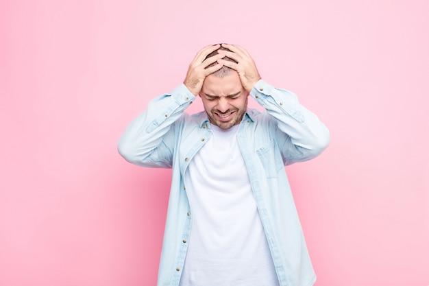 Jonge knappe man die zich gestrest en gefrustreerd voelt, zijn handen naar het hoofd heft, zich moe, ongelukkig voelt en met migraine tegen een vlakke muur