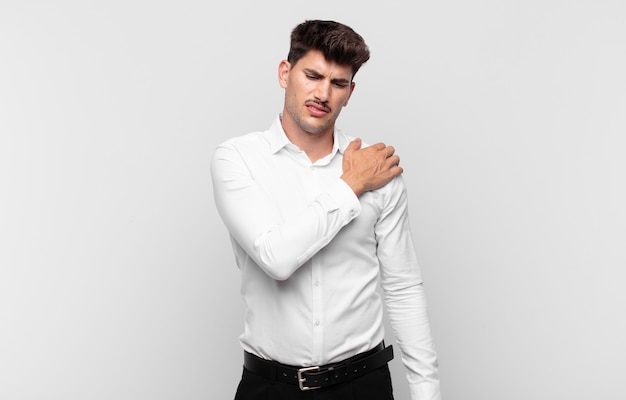 Jonge knappe man die zich moe, gestrest, angstig, gefrustreerd en depressief voelt, last heeft van rug- of nekpijn