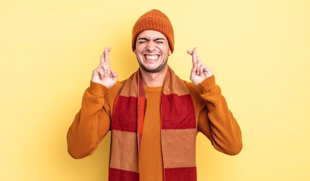 Jonge knappe man die zich nerveus en hoopvol voelt, vingers kruist, bidt en hoopt op geluk