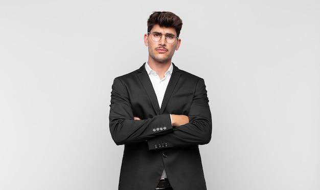 Jonge knappe man die zich ontevreden en teleurgesteld voelt, ernstig, geïrriteerd en boos kijkt met gekruiste armen