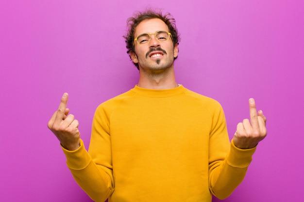 Jonge knappe man die zich provocerend, agressief en obsceen voelt, de middelvinger wegknipt, met een opstandige houding tegen de paarse muur