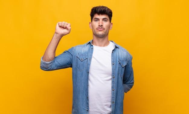 Jonge knappe man die zich serieus, sterk en rebels voelt, vuist opstekend, protesteert of vecht voor revolutie