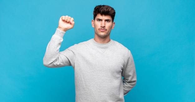 Jonge knappe man die zich serieus, sterk en rebels voelt, zijn vuist opheft, protesteert of vecht voor revolutie
