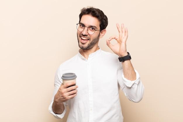 Jonge knappe man die zich succesvol en tevreden voelt, glimlachend met wijd open mond, goed teken met hand makend
