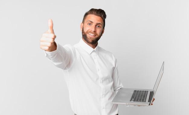 Jonge knappe man die zich trots voelt, positief glimlacht met duimen omhoog en een laptop vasthoudt