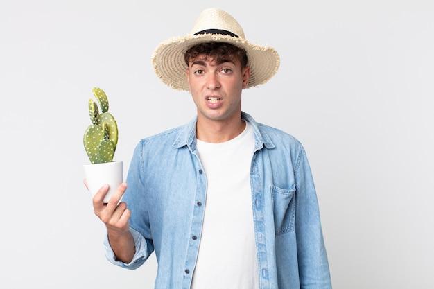 Jonge knappe man die zich verbaasd en verward voelt. boer met een decoratieve cactus