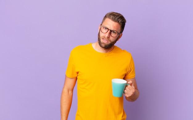Jonge knappe man die zich verbaasd en verward voelt. en een koffiemok vasthouden