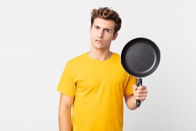 Jonge knappe man die zich verbaasd en verward voelt en een kookpan vasthoudt