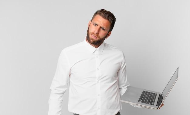 Jonge knappe man die zich verbaasd en verward voelt en een laptop vasthoudt