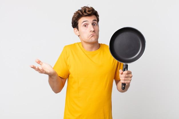 Jonge knappe man die zich verbaasd en verward voelt en twijfelt en een kookpan vasthoudt