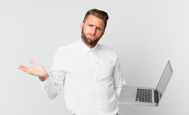 Jonge knappe man die zich verbaasd en verward voelt en twijfelt en een laptop vasthoudt