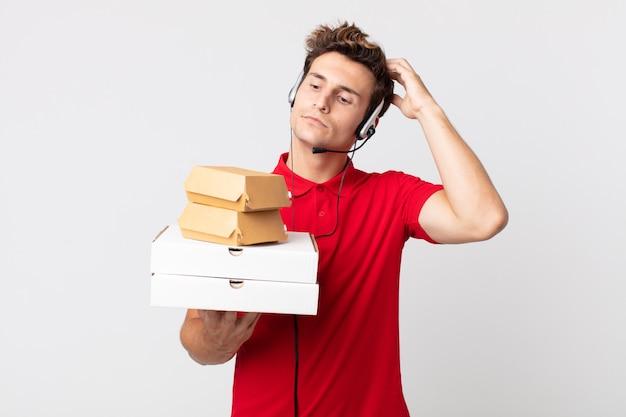 Jonge knappe man die zich verbaasd en verward voelt, hoofd krabben. afhaal fastfood concept