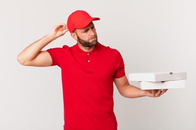 Jonge knappe man die zich verbaasd en verward voelt, hoofd krabben. pizza bezorgconcept