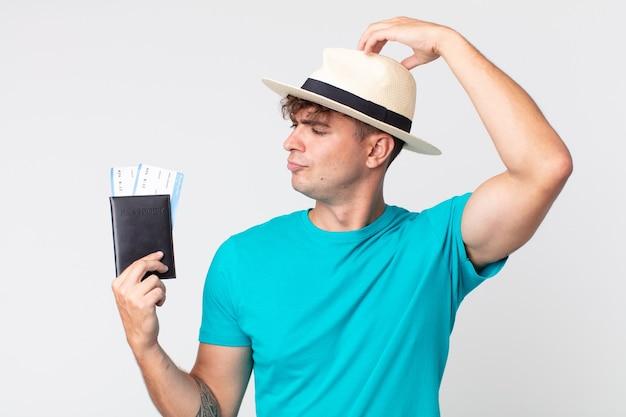 Jonge knappe man die zich verbaasd en verward voelt, hoofd krabben. reiziger met zijn paspoort